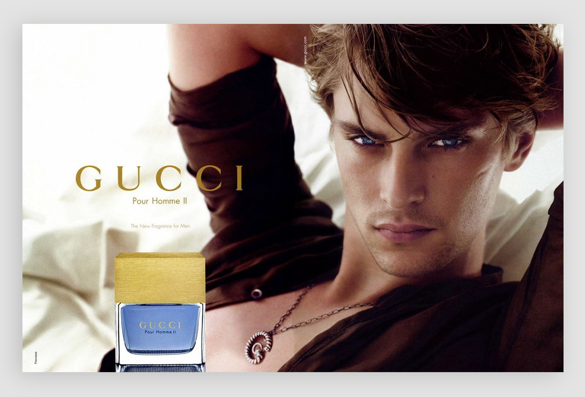 A photo of a man leaning against a pillow with a Gucci cologne in the corner of the ad.