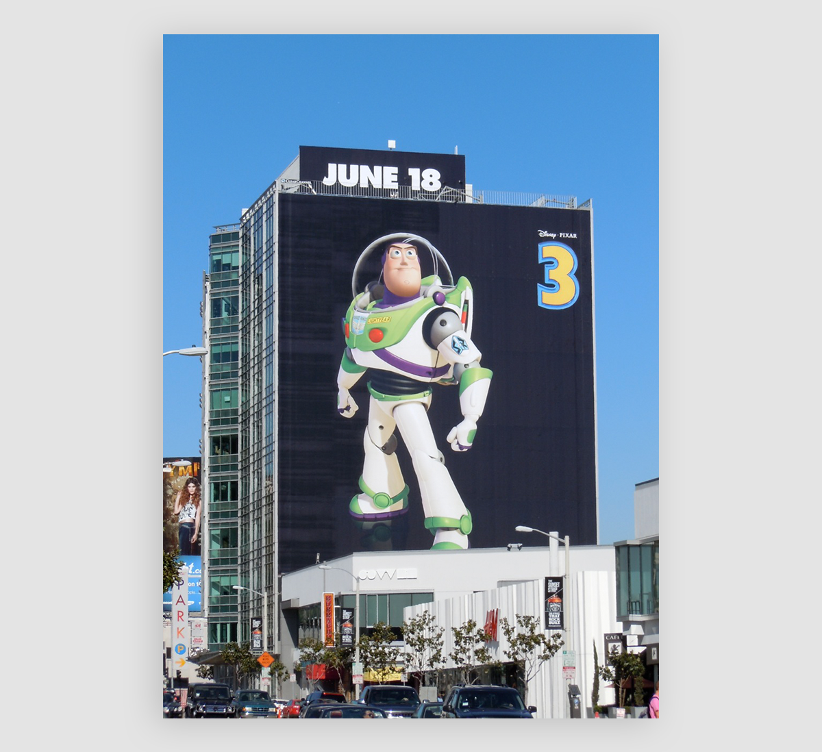 A photo of Buzz Lightyear on a giant billboard on the side of a large building.